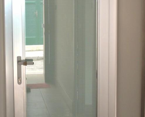 Porta finestra profilo Schuco AWS65 effetto ossidato argento a 20 micron con maniglia interna con chiave. Composizione vetro: vetro Visarm 33.1 Planibel Light + vetro Visarm 66.8 Classe di resistenza secondo EN356P6B=30/50 colpi di martello e di ascia + Camera da 27/28 mm con all'interno della camera tenda veneziana morotizzata SL22M Pellini