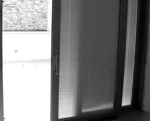 Alzante scorrevole Schuco ASS70HI a taglio termico finitura est. marrone RAL8019 e int. effetto inox dotati di maniglia interna vaschetta esterna. Composizione vetro: vetro Visarm 33.1 Planibel Light + vetro Visarm 66.8 Classe di resistenza secondo EN356P6B=30/50 colpi di martello e di ascia + Camera da 27/28 mm con all'interno della camera tenda veneziana morotizzata SL22M Pellini