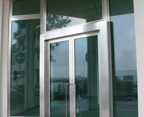 Serie porta e finestra Schuco AWS/ADS65 a taglio termico effetto acciaio lucido. Composizione vetro: Visarm antisfondamento 66.2 energy a basso controllo solare + camera da 15 con gas argon + Visarm antisfondamento 66.2 interno